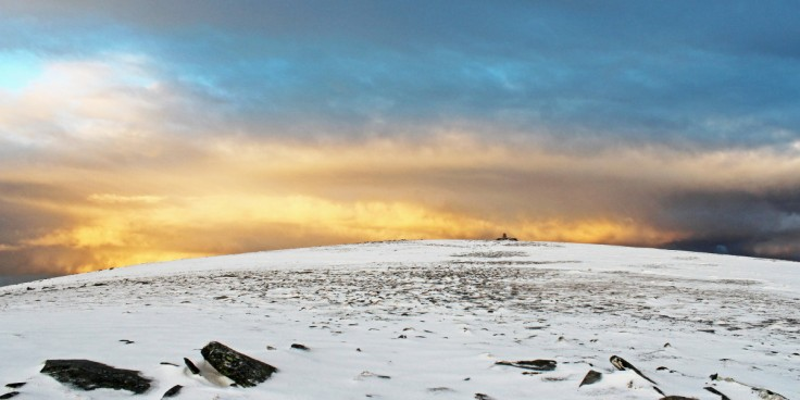 Photo of the Ben Hope summit plateau with the trig point prominent and afternoon sunlight highlighting the clouds to the north