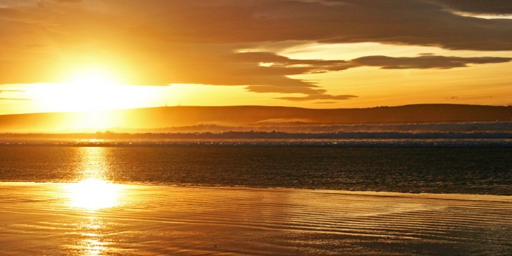 Photo of sunset from Dunnet Beach with the sun descending behind Olrig hill near Castletown