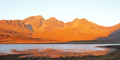 Photo of Bla Bheinn (Blaven) bathed in early morning light as the sun rose behind.