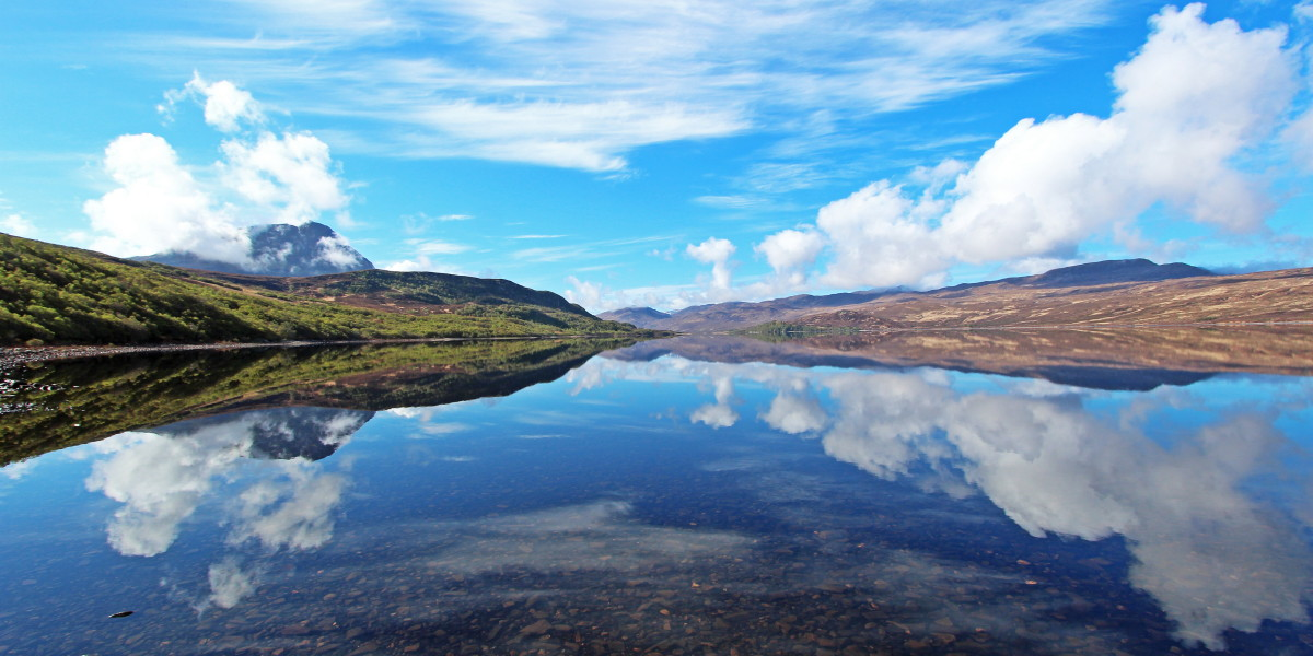 Photo of reflections on Loch Hope on a beautiful, still May morning with Ben Hope, semi shrouded in morning low cloud, on the left