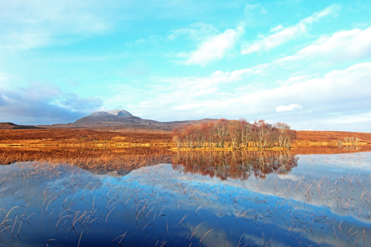 Photo of Canisp reflected in the calm water of Assynt's Loch Awe