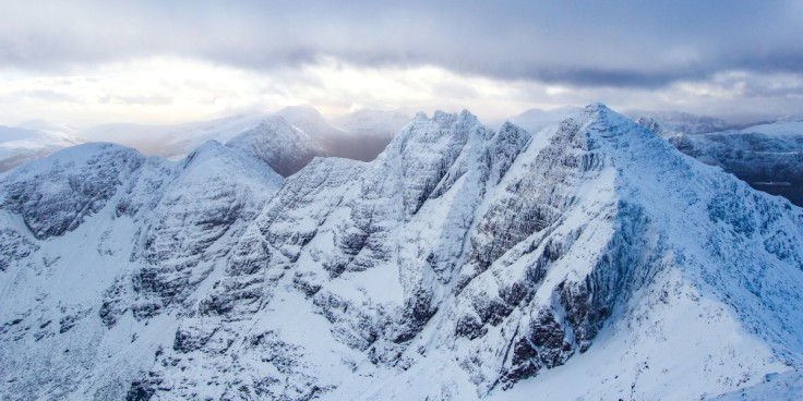Photo of a wintry classic view of An Teallach across Toll an Lochain to Sgurr Fiona and the Corrag Bhuidhe pinnacles. The remote hills of the Fisherfield Forest are beyond