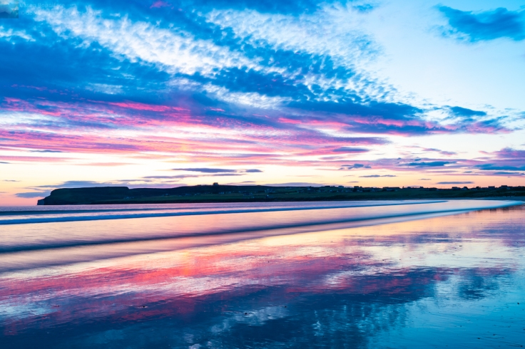 Photo of sunset reflections on the wet surface of Dunnet Beach.