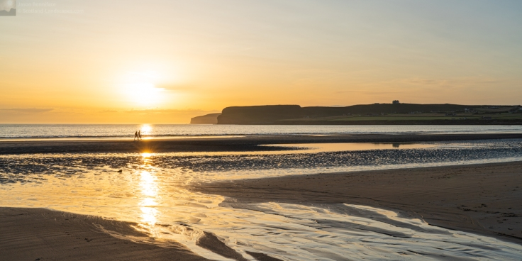 Photo of a couple strolling along the shoreline at Dunnet Beach as the sun descends