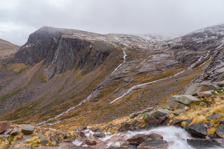 Photo of The Shelter Stone Crag and Carn Etchachan with plenty of water flowing from the plateau down the Allt Coire Domhain, Feith Buidhe, and Garbh Uisge streams into Loch Avon.